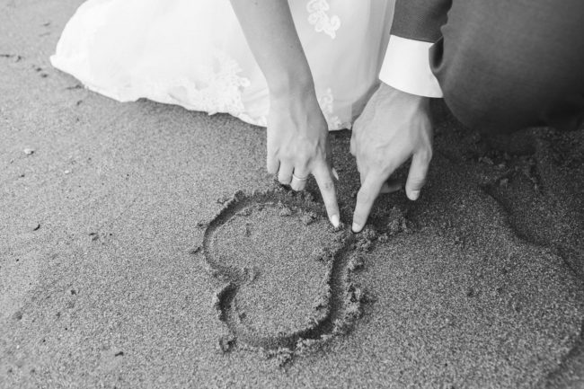 bride and groom drawing a heart shape on the sand